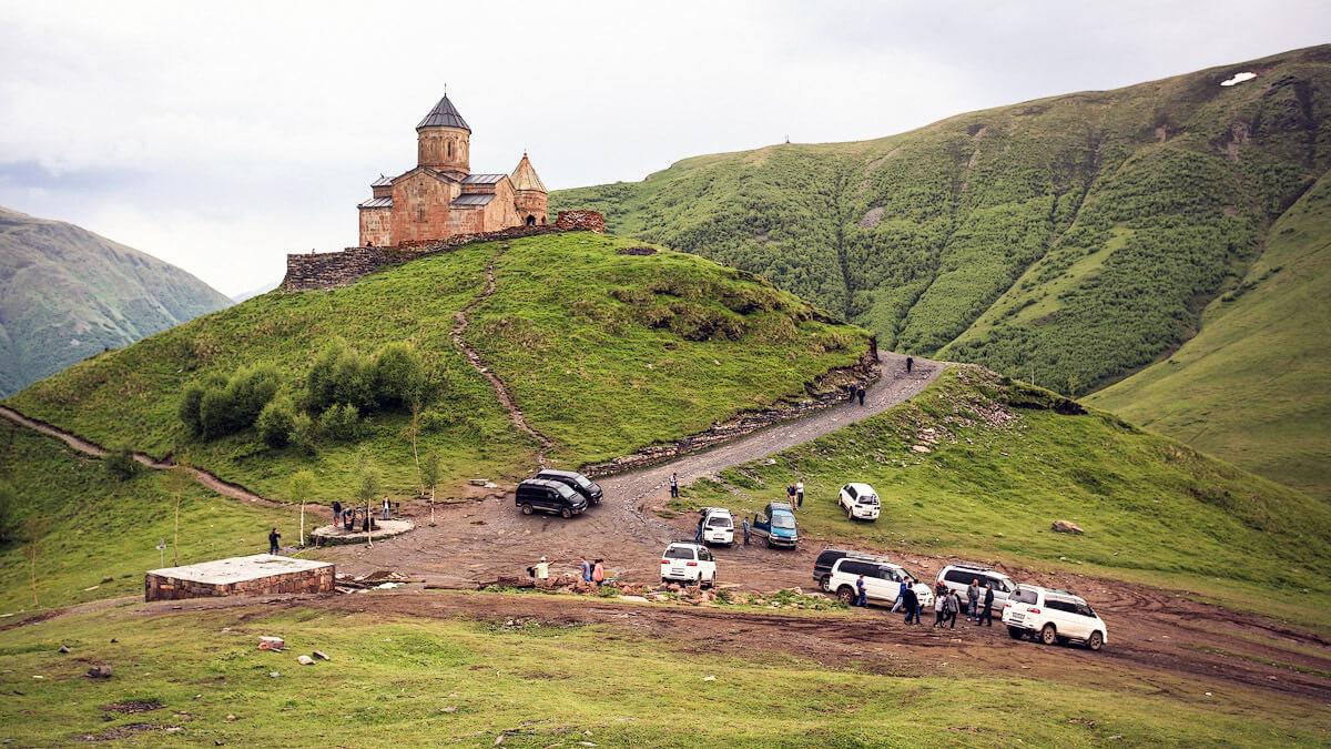 У подножья горы стоят таксисты и автомобили жителей Казбеги