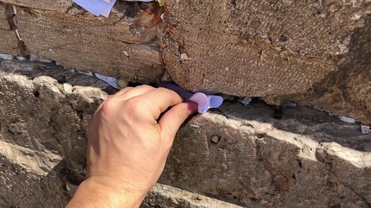 Раввин относит записки в Стену