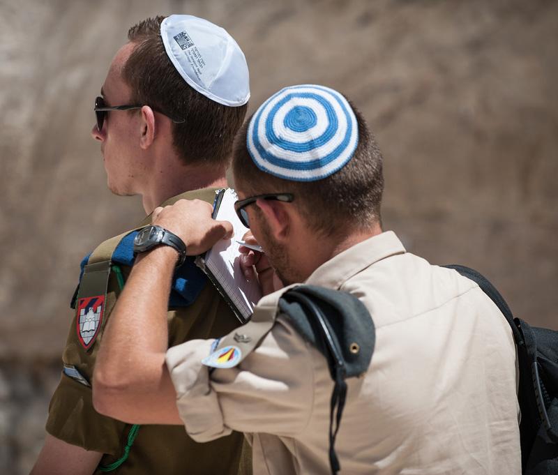 Солдат пишет записку в Стену Плача