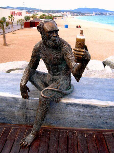 Скульптура человека-обезьяны с бутылкой